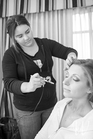 makeup artist applying airbrush makeup to a bride