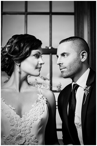 black and white photo of bride and groom close together looking at each other